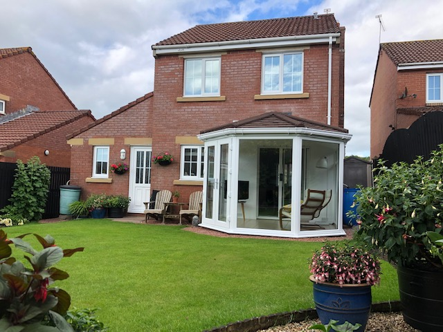 External view of warm roof on brick built house including garden